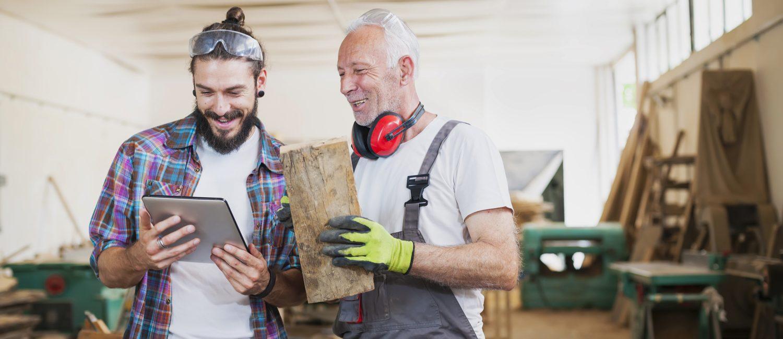 Senior and young carpenter working at workshop using digital tablet